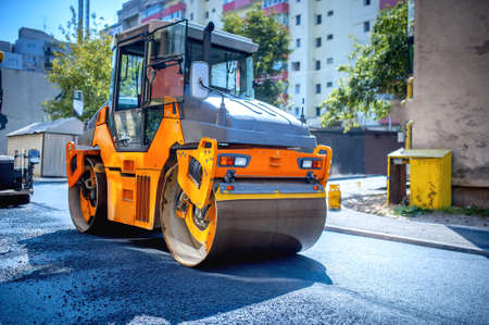 roller compactor: Heavy tandem Vibratory roller compactor working on asphalt pavement at road repairing