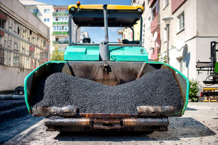 blacktopping: industrial paver laying fresh asphalt and bitumen pavement on top of gravel layer during road construction