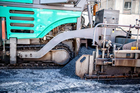 blacktopping: asphalt paver machine during road construction and repairing works