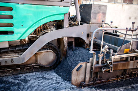asphalting: Industrial pavement truck or machine laying fresh bitumen and asphalt Stock Photo