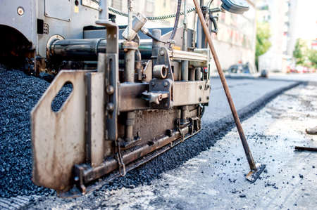 asphalting: close-up of asphalting machinery and tools working at industrial highway road construction site