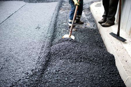 asphalting: worker with shovel doing manual labor at road construction with asphalt and fresh bitumen
