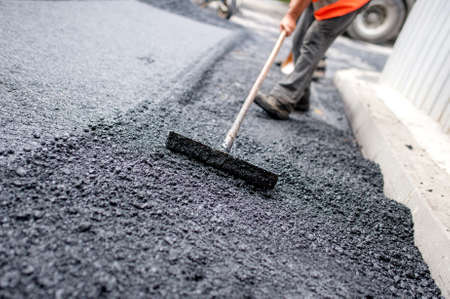 Worker levelling fresh asphalt on a road construction site, industrial buildings and teamwork