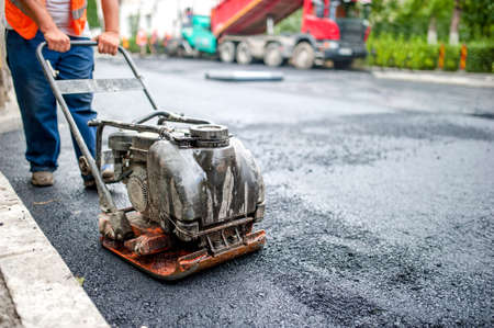 asphalt worker at road repairing and construction site with manual compactor plate photo