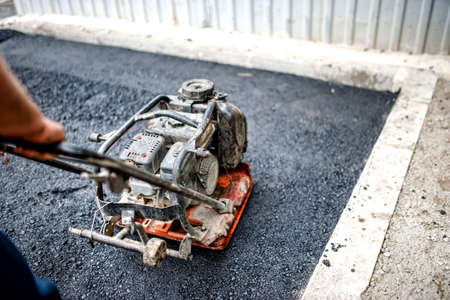 compactor: close-up of asphalt worker in construction site with manual compactor plate