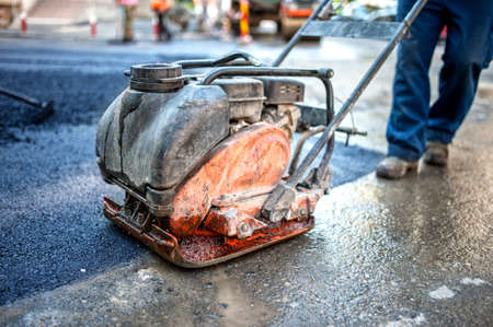 compactor: asphalt worker at road construction site with compactor plate and tools