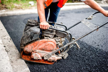 asphalt worker at road construction site with compactor plate and tools photo