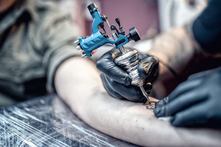 in arms: tattoo artist drawing on client with special tools