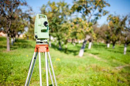 teodolito: Levantamientos estación total y en la medición de equipos de ingeniería en el trabajo en el jardín o bosque