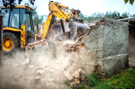 불도저는 작은 건물의 콘크리트 벽돌 벽을 부수고 스톡 콘텐츠