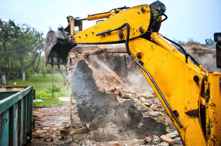 demolishing: bulldozer and excavator demolishing concrete brick walls