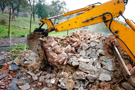 recycle area: excavator on demolition site loading bricks and concrete walls