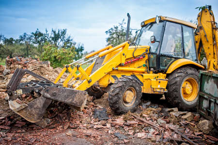 break down: Hydraulic crusher, industrial excavator machinery working on site demolition
