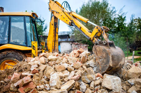 industrial hydraulic excavator on construction and demolition site, recycling construction waste with bulldozer