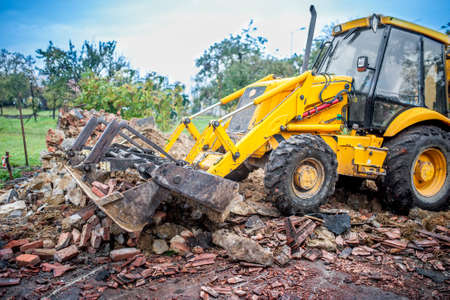 bulldozer working at demolition site, cleaning debris of bricks and walls