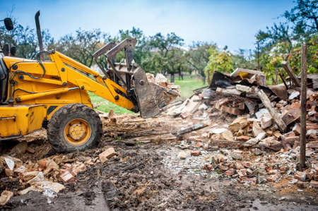work area: Hydraulic bulldozer crusher, industrial excavator machinery working on site demolition