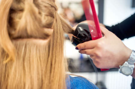 long lasting: Blonde woman at hair salon using a professional tool for creating curls with long lasting effect. Beautiful woman using diferent styling salon tools Stock Photo