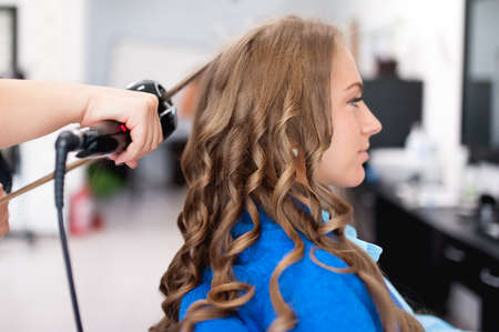 professional hairdresser using curiling iron for hair curls at salon