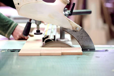 assemblies: wood factory worker cutting wood boards with sliding compound mitre saw with sharp blade