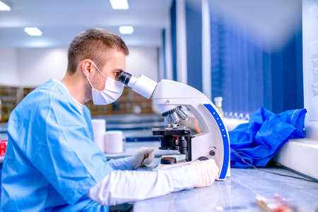 Scientist working in chemistry laboratory, examining samples at microscop photo