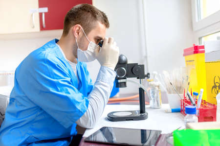 male chemist working with microscope in laboratory photo