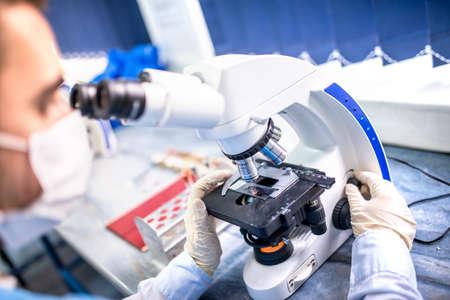 Chemiker Forscher arbeiten mit Mikroskop für forensische Beweise