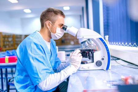 laboratorio clinico: Cient�fico de sexo masculino, qu�mico trabaja con el microscopio en laboratorio farmac�utico