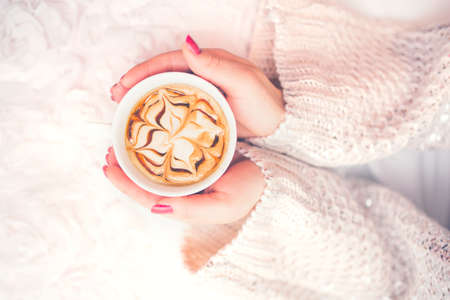 bed and breakfast: Woman hands holding a cup of hot coffee, espresso on a winter, cold day. View from top, soft vintage effect Stock Photo