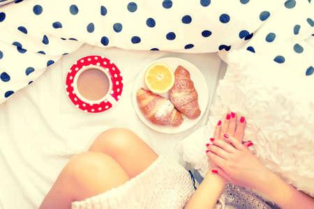 jeune fille: Close-up de jambes de femme et le petit d�jeuner au lit avec des croissants, caf� et jus d'orange sur un dimanche matin paresseux Banque d'images