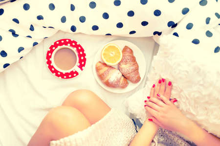 Close-up of woman legs and breakfast in bed with croissants, coffee and orange juice on a lazy sunday morning
