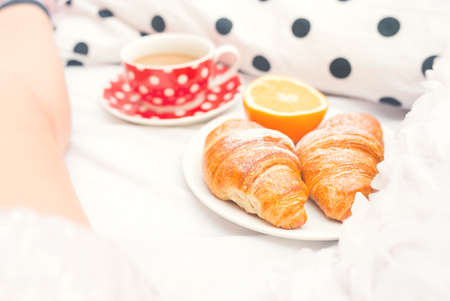 roomservice: Croissants, caramel cookies and chocolate with milk as breakfast in bed as romantic gesture for girl