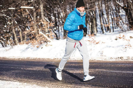 hardcore: Young athlete going for a run outdoor in snow, hardcore training and jogging