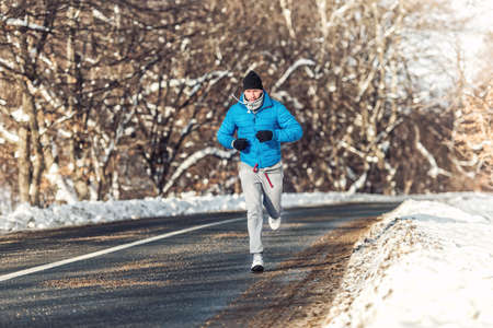 Man fitness concept - running and jogging, outdoor training in snow on a cold sunny day photo