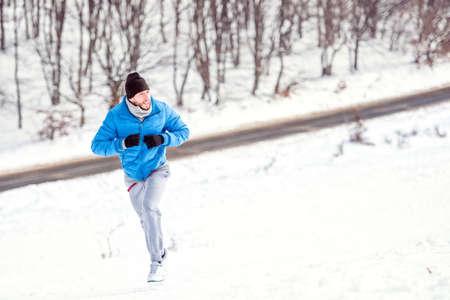 hombre deportista: Joven atleta corriendo en la nieve para un entrenamiento saludable