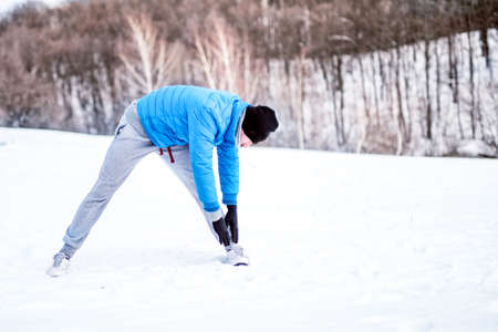 strenght: Fit man training and stretching outdoor in snow