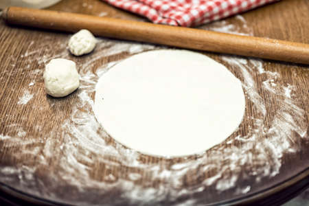 Pizza dough with rolling-pin and flour, on wooden table photo