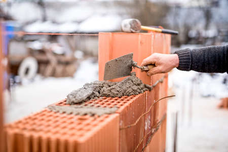 gypsum: Construction site on a winter day with worker building brick walls with mortar and bricks Stock Photo