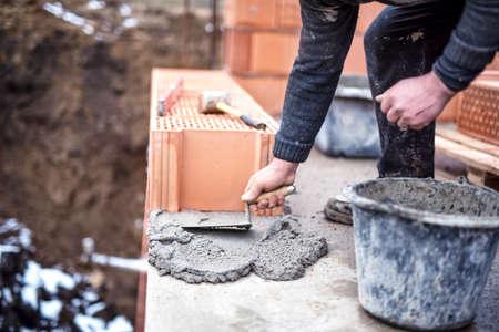 paredes de ladrillos: Trabajador de la construcción utilizando la paleta y el cemento para la instalación de la fábrica de ladrillo