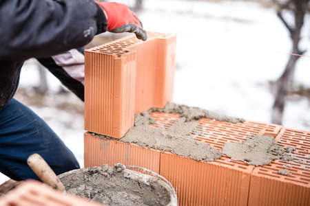 buliding: Worker buliding brick walls at house construction site, bricklayer and cement Stock Photo