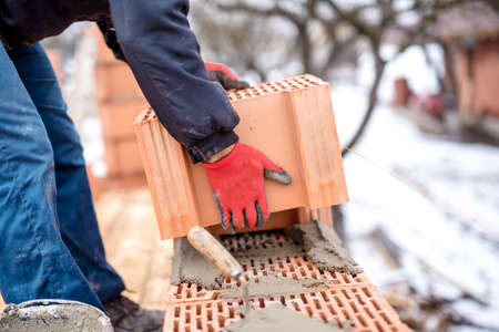 mud and snow: close-up of construction worker, bricklayer building new house with brick walls Stock Photo