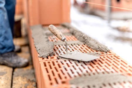 Detail of construction site, trowel or putty knife on top of brick layer Imagens