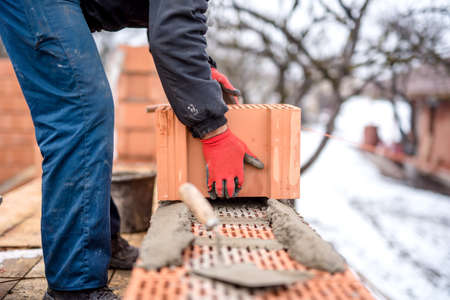 putty knives: construction site and mason bricklayer working with bricks, cement and mortar for building new house