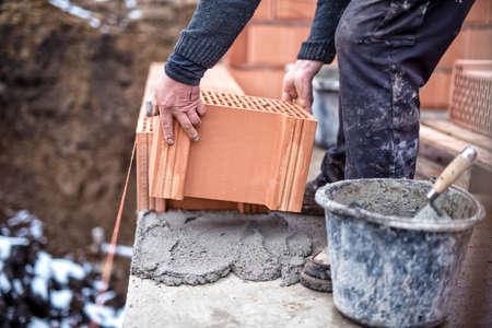 Bouwplaats van nieuw huis, arbeider bouw van de bakstenen muur met troffel, cement en mortel