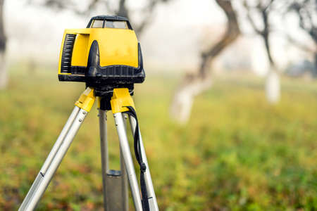 surveying: Surveying measuring equipment level theodolite on tripod on a foggy day in construction site