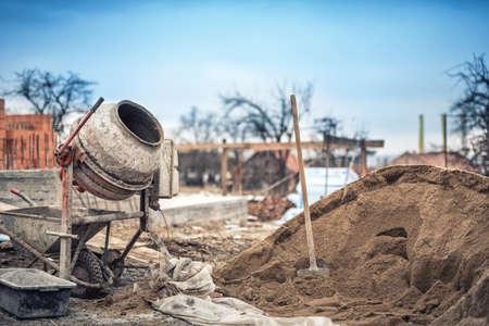 cemento: Cemento máquina mezcladora en el sitio de construcción, herramientas y arena Foto de archivo