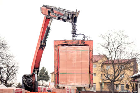 Crane delivers a brick pallet at building construction site, isolated on white sky