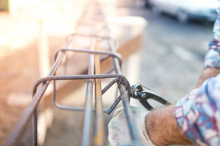 Details of infrastructure - Construction worker hands securing steel bars with wire rod for reinforcement of concrete