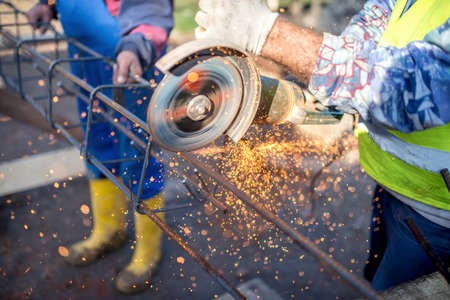 industrial site: industrial engineer working on cutting a metal and steel bar with angle grinder, construction site details