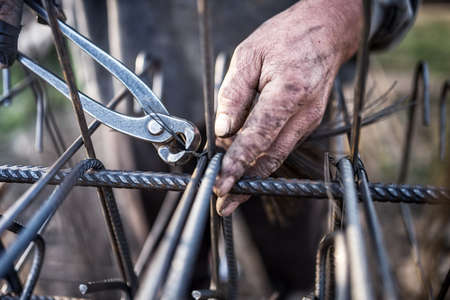 Details of construction worker - hands securing steel bars with wire rod for reinforcement of concrete or cement