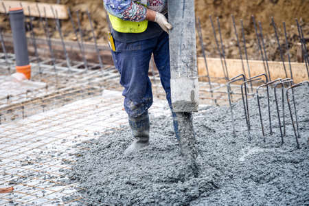 building construction worker pouring cement or concrete with pump tube photo